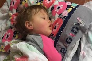 toddler sleeping on bed