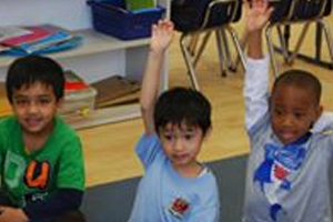 children raise hands for answering the question